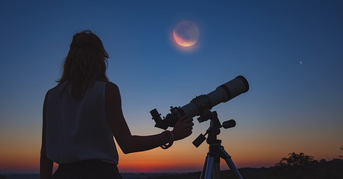 person looking at the moon with a telescope