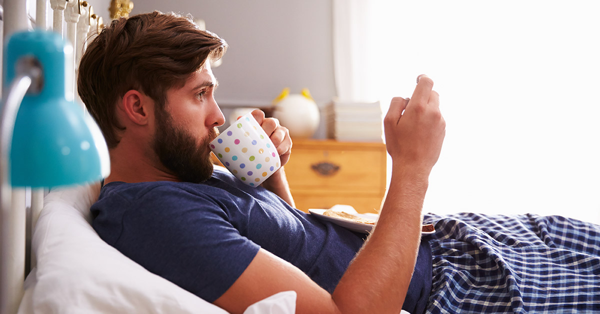 phone removed from picture of man in bed sipping coffee