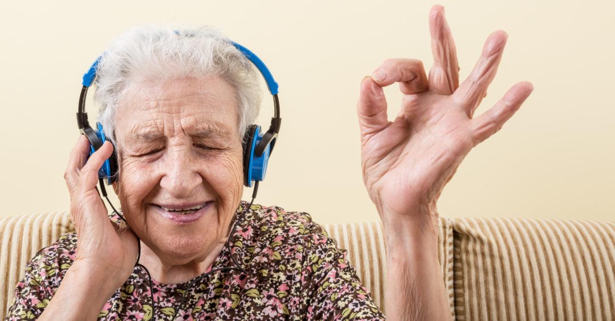 Elderly woman wearing headphones and enjoying some music