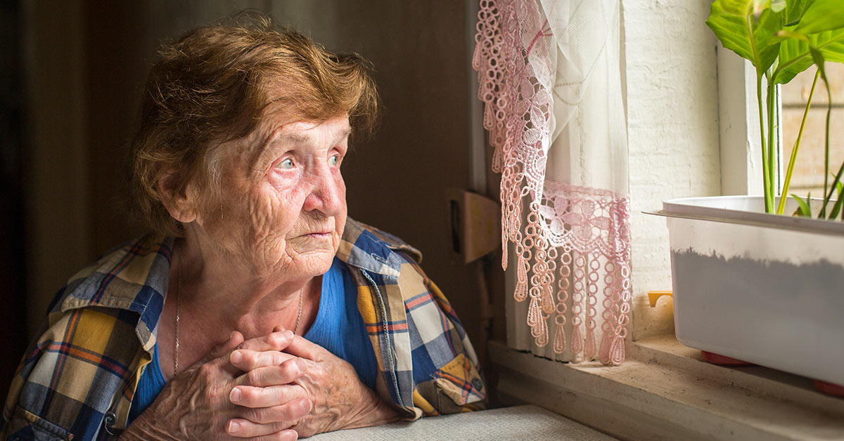 lonely senior looking out a window