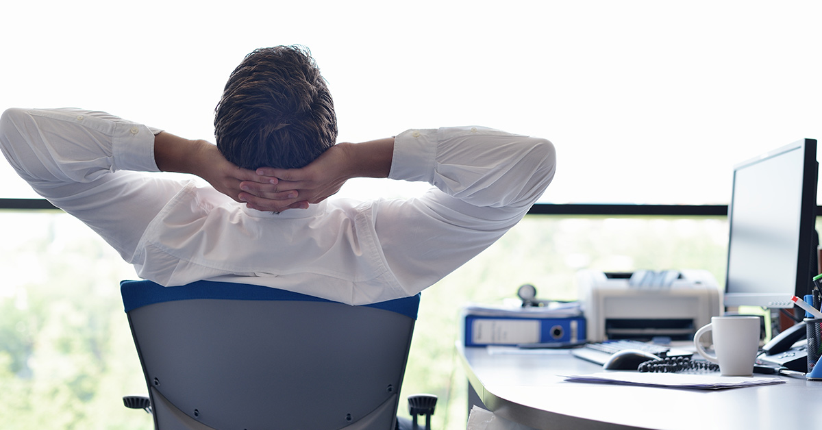 man leaning back in office chair with hand clasped behind his head
