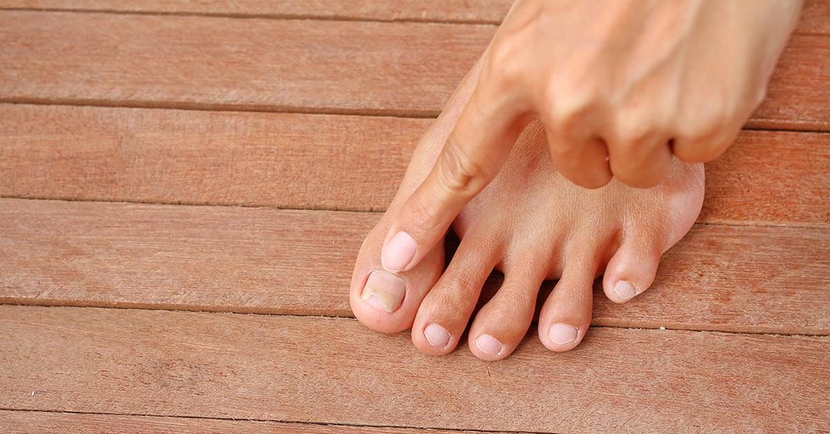person pointing to their toenail