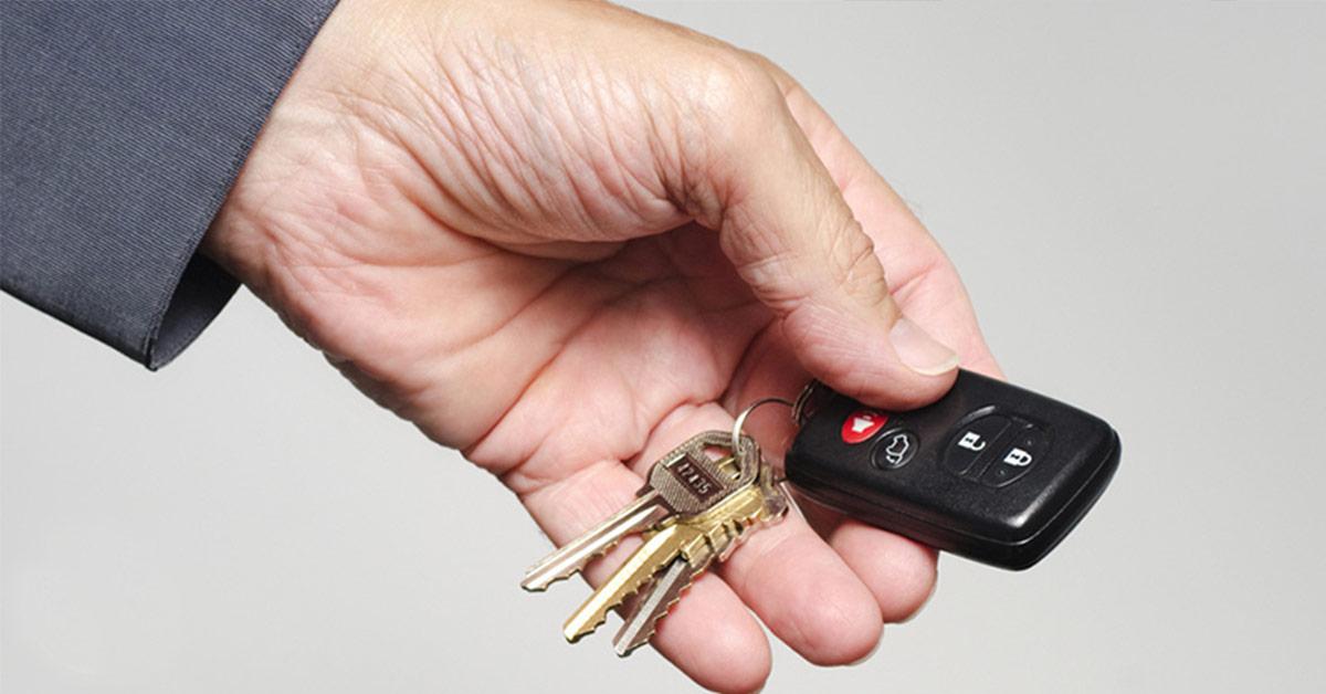 person holding a car key fob